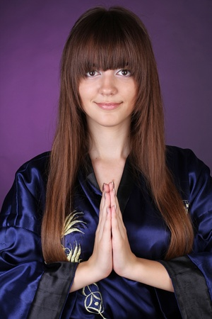 Woman with praying hands over dark purple photo