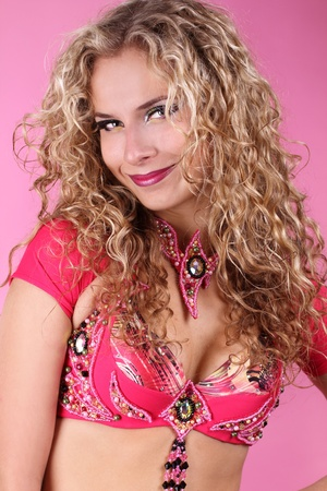 Happy smiling belly dancer girl with curly blond hair over ping background Stock Photo - 11087410