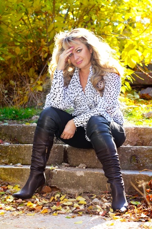 Business woman sitting on stairs walking outdoors in autumn photo