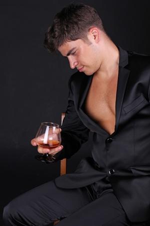 Closeup of man holding glass of cognac on dark background photo