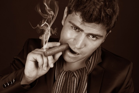 Close up portrait of man smoking a cigarette on a dark photo