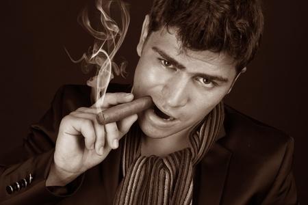 gigolo: Close up portrait of man smoking a cigarette on a dark Stock Photo