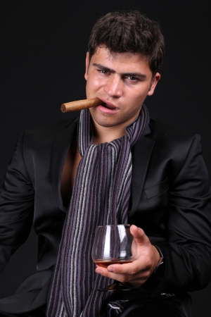 Man with a cigar and a glass of cognac on dark background photo