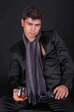 drunks: portrait of a young relaxing sexy man with glass of cognac
