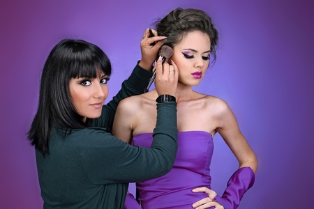 Professional Make-up artist doing model makeup at work photo