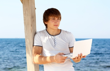 Young man with laptop look away at beach photo