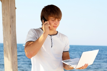 Young man with mobile phone using laptop at beach photo
