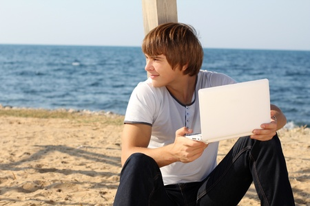 only young men: smiling man with laptop outdoor on beach, outdoors