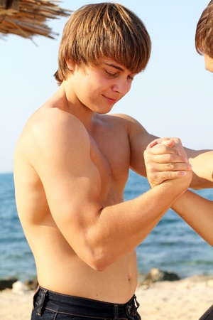 Strong young man, arm wrestling on the beach photo