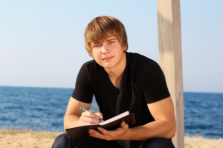 blue sky thinking: Attractive young man with writing pad on the beach