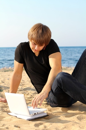 Business young guy working at laptop over beach photo