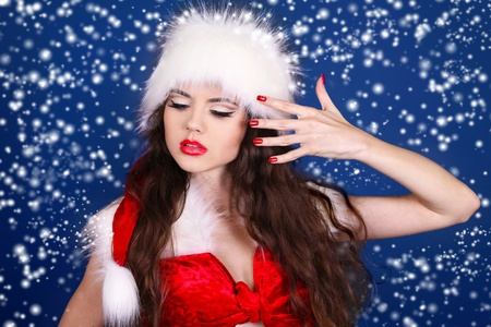 Girl in Santa Claus red dress posing on snow background photo