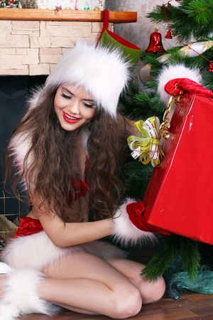 Girl with surprise gift red box in interior photo
