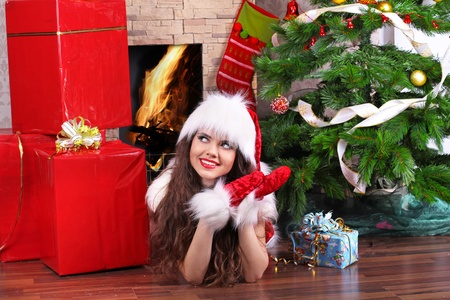 Home, woman in Santa suit lying near Christmas tree and gift photo