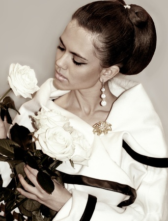 womanliness: Fashion young woman with hairstyle and roses in hands