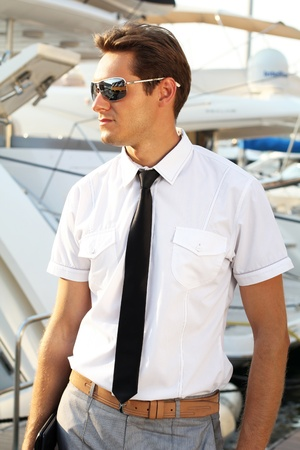 Man captain in a white shirt near the yacht, looking away