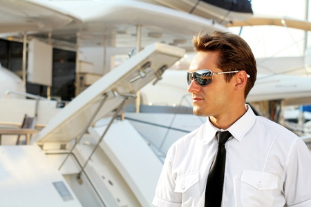 Handsome man, a serious captain in a white shirt near the yacht, looking away Stock Photo