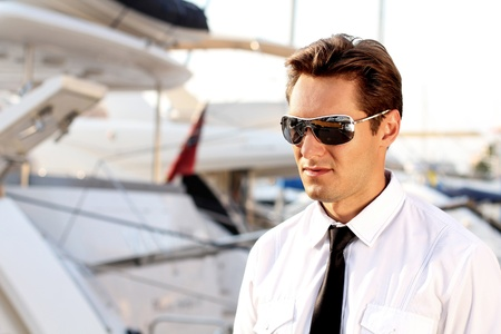 Portrait of Casual man wearing sunglasses,  over yacht outdoors background photo