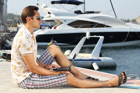 Handsome businessman running a laptop on the shore near the yacht boat at rest photo