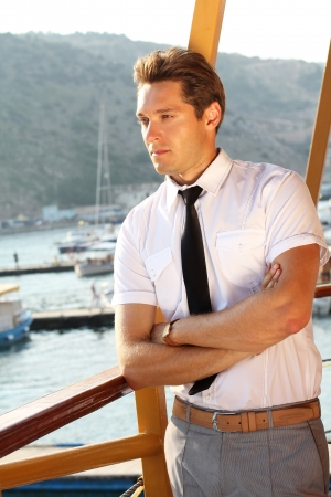 handsome man in a white shirt looking away, sunshine outdoors, sea port photo
