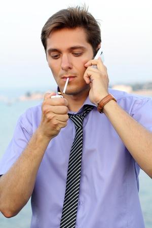 hombre fumando: Joven empresario con teléfono, guapo hombre fumando cigarrillos, al aire libre Foto de archivo