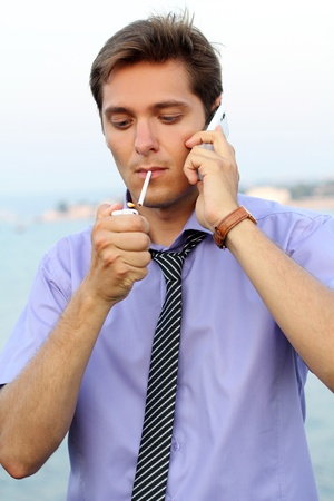 Young businessman with telephone,handsome man smoking cigarette, outdoors