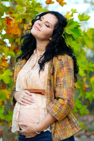 Pregnant woman caressing her belly, outdoors
