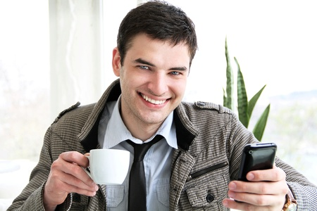 Happy young businessman using mobile phone in business building, smiling. Stock Photo - 11866559