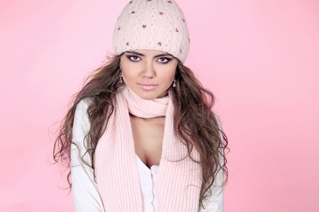 Young beautiful woman wearing winter clothing over pink photo
