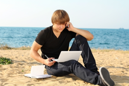 casual young business man using laptop on the beach photo