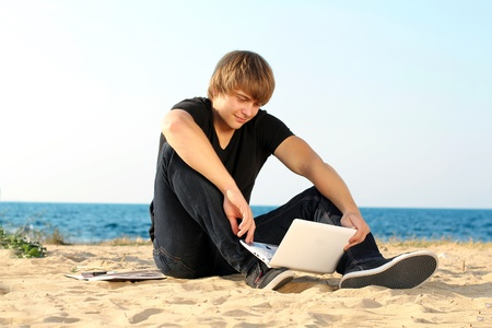Young student man using laptop on the beach photo