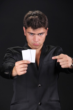 Portrait of man with blank card isolated on black background.  photo