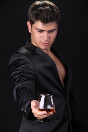 Focus on  glass of cognac, man on dark background Stock Photo - 11933842