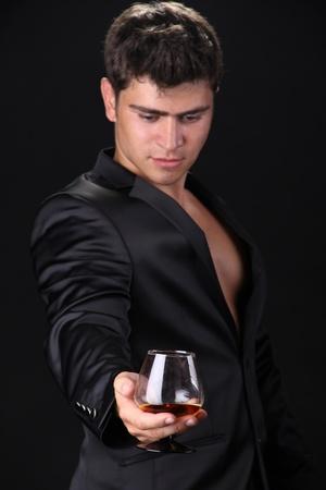 Focus on  glass of cognac, man on dark background Stock Photo - 11933842