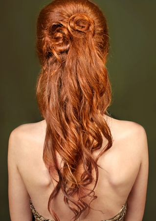 back straight: Red long curly healthy hair of woman on green background