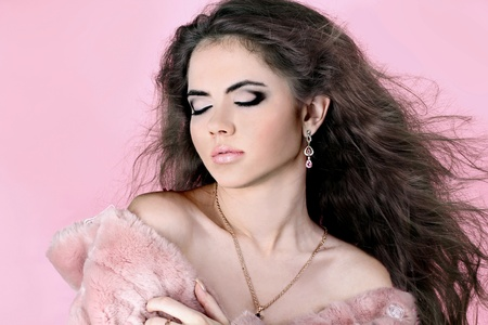 Sexy woman model with smart fair hair in  fur coat , over pink photo