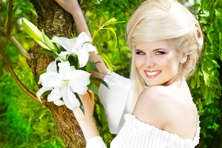 Portrait beauty happy blonde young woman with white lily, nature photo