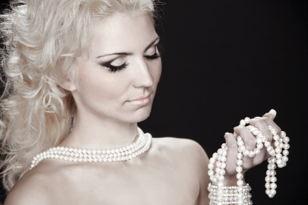 Beautiful fashion blonde woman with pearls, studio salon photo