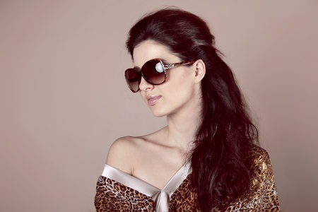 Fashion Woman in sun glasses over beige photo