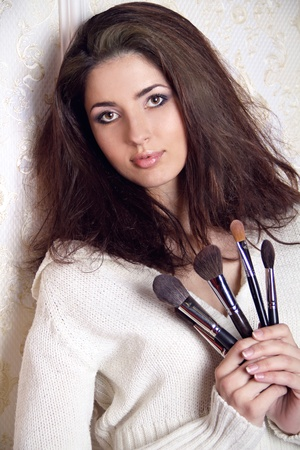 Beautiful woman with makeup brushes near her face casually leaning against the wall photo