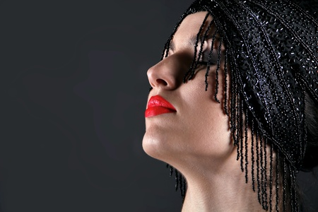 Fashion model face with red lip on black background photo