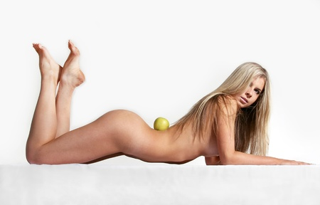 Naked woman lying with perfect body line in the studio on white, green apple Stock Photo - 13122384