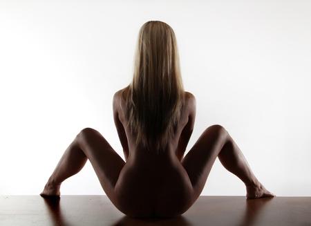 jeune femme nue: Portrait de retour superbe jeune femme nue posant sur le bureau