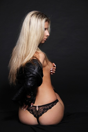Sexy blond woman in black lingerie posing on black background