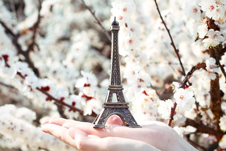 Tiny Eiffel tower on the hands, dreams of about traveling in Paris photo