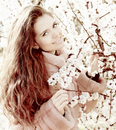 Young attractive smiling woman outdoors portrait, flowers background photo