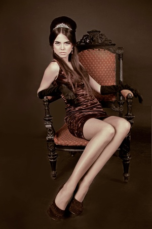 Elegant woman with fashion hair style sitting on vintage armchair in dark interior photo