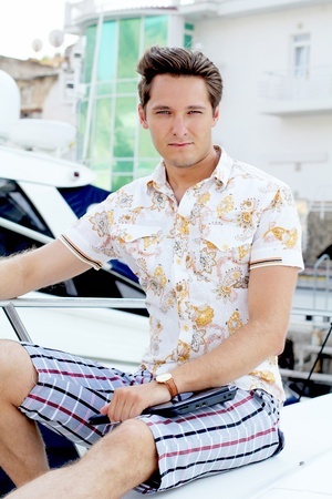 Handsome man with laptop sitting on white yacht photo