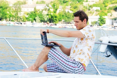 Working man with laptop sitting on white yacht, beach photo