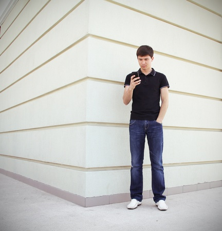 Handsome student using a mobile phone with perspective wall copyspace Stock Photo - 13599359